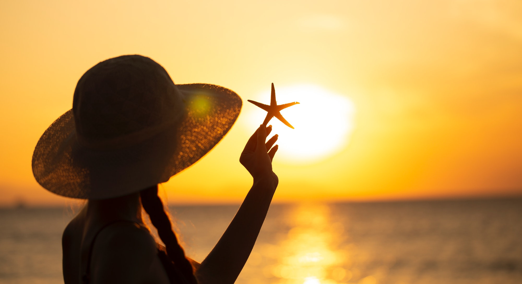 young woman in hat with starfish on the beach