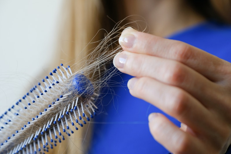 A woman holds a comb in her hands, cleans it from fallen hair after combing, in the bathroom. The co...