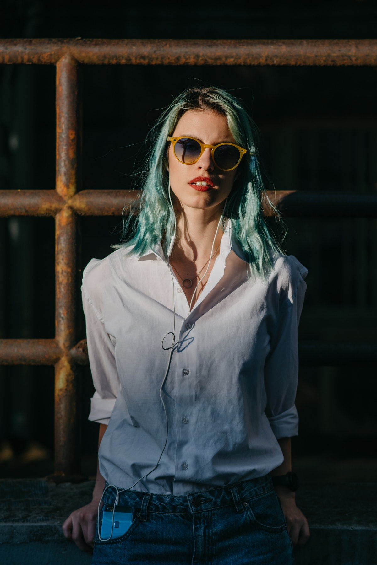 Young woman with blue hair looking at camera, after reading about the emotional meaning of the Augus...