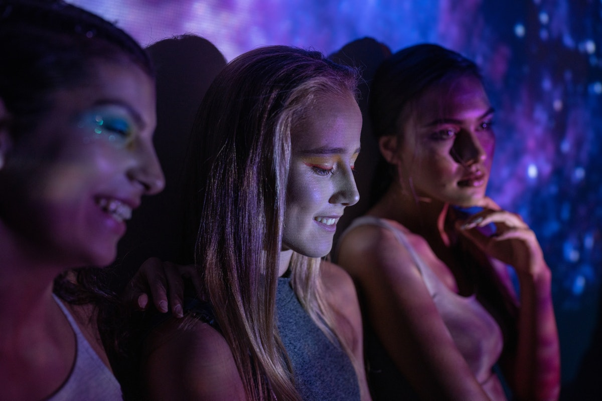 Photo of a teenage girls illuminated with neon lights, having fun together during the August 2021 fu...