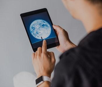 HONG KONG, HONG KONG - OCTOBER 4: A man holds an Apple iPad Mini as he uses WeChat app on October 4,...