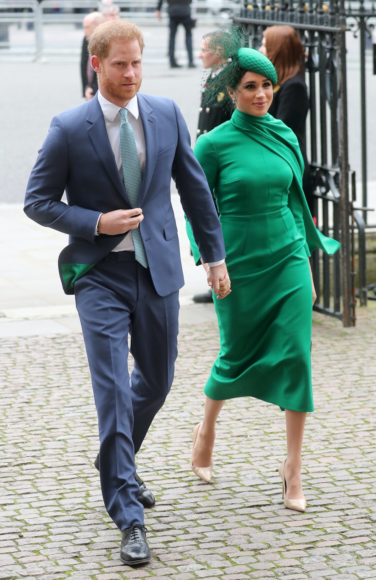 Meghan Markle is shown here in an emerald green ensemble consisting of a dress and matching scarf an...
