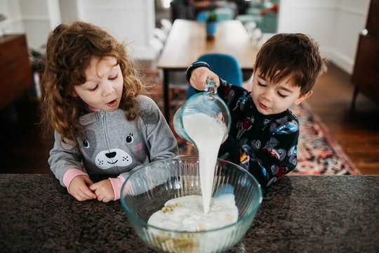 two kids pouring batter into a bowl
