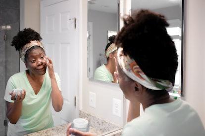 Close-up of mid adult black woman applying facial moisturizer in bathroom mirror