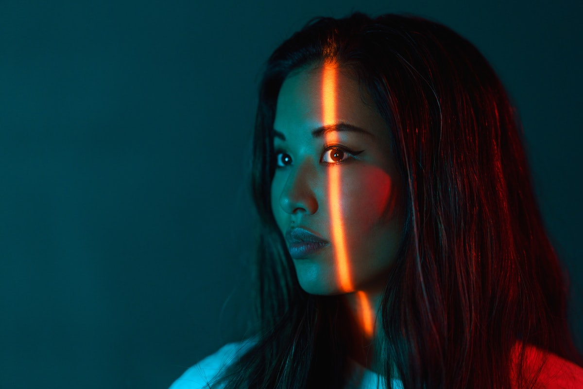 A portrait of a beautiful woman lit by neon colored lights during the August 2021 full moon in Aquar...