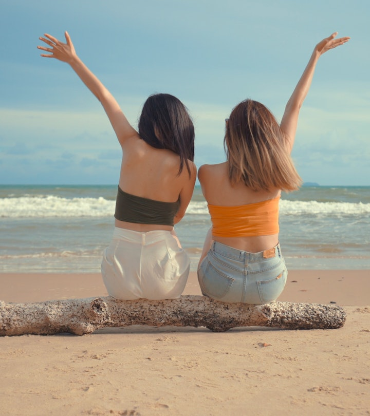 sisters sitting on a piece of driftwood on the beach, looking at the ocean