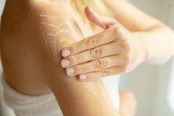 woman putting lotion on arm after shower