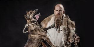 Viking warrior Odin man holding a dog and an authentic weapon