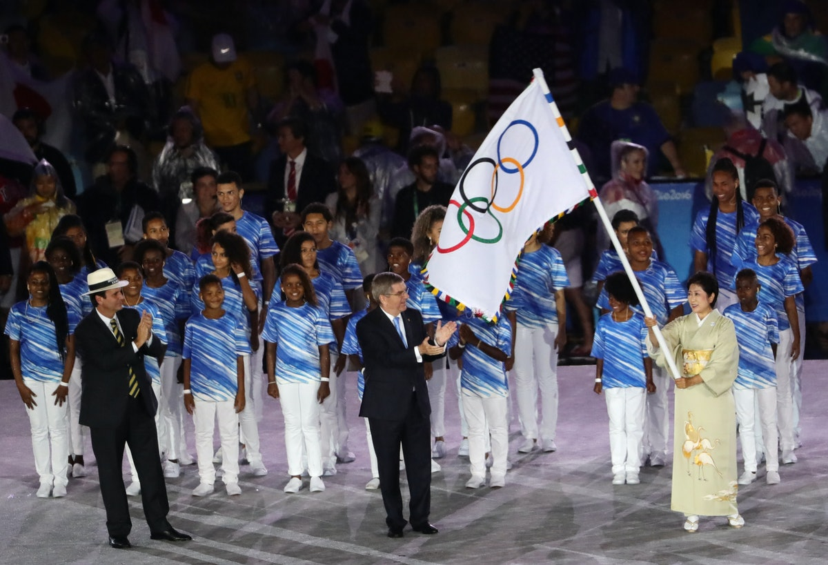 The governor of Tokyo Yuriko Koike waves the Olympic Flag as IOC President Thomas Bach and the mayor...