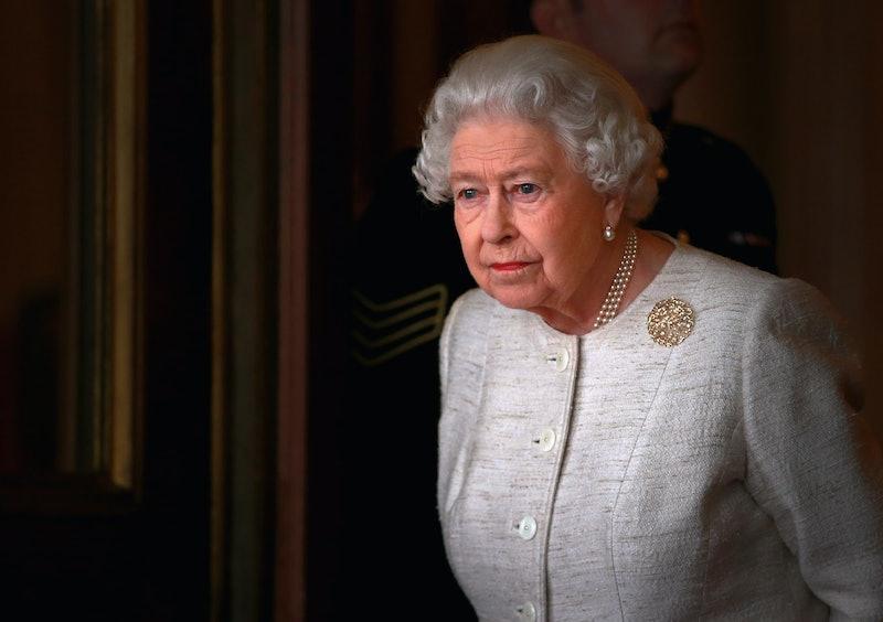 Queen Elizabeth II standing in a doorway.