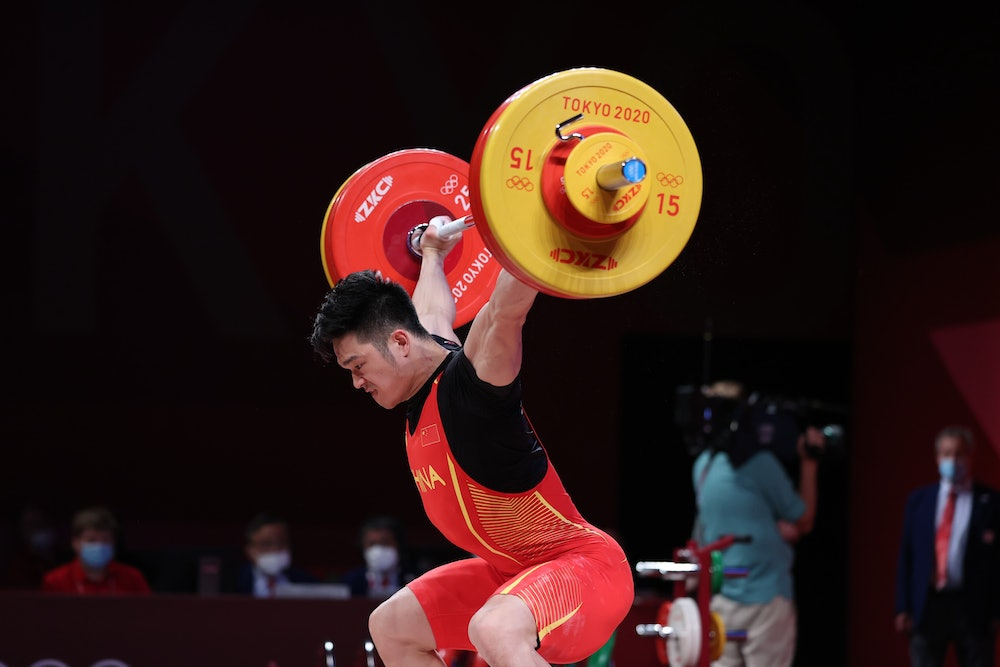 Shi Zhiyong of China competes during the men's 73kg weightlifting event of the Tokyo 2020 Olympic Ga...