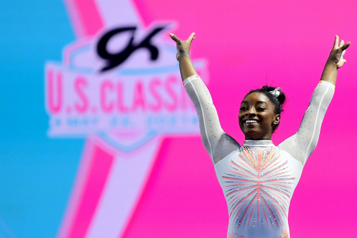 Simone Biles is shown wearing a embellished white leotard while standing in front of a pink and blue...