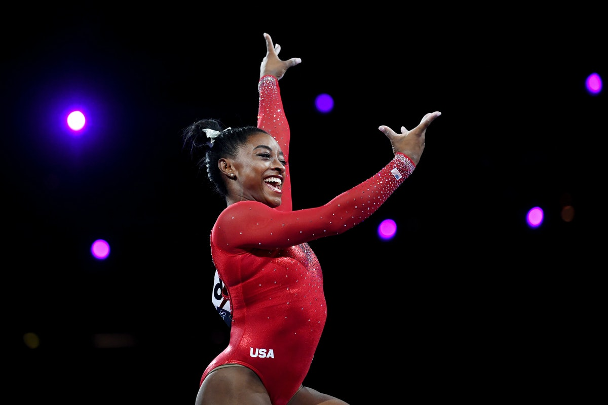 Simone Biles is wearing a red leotard and is smiling while performing at a competition.