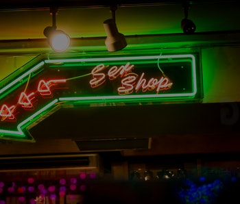 Neon lights posting the way to sex shops in the soho district of Central london