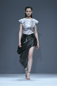 A model walks the runway showing how to wear an asymmetrical skirt that's both a mini and a maxi ski...