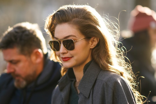 PARIS, FRANCE - FEBRUARY 26: Gigi Hadid wears sunglasses, a gray jacket, a green wool pullover, outs...