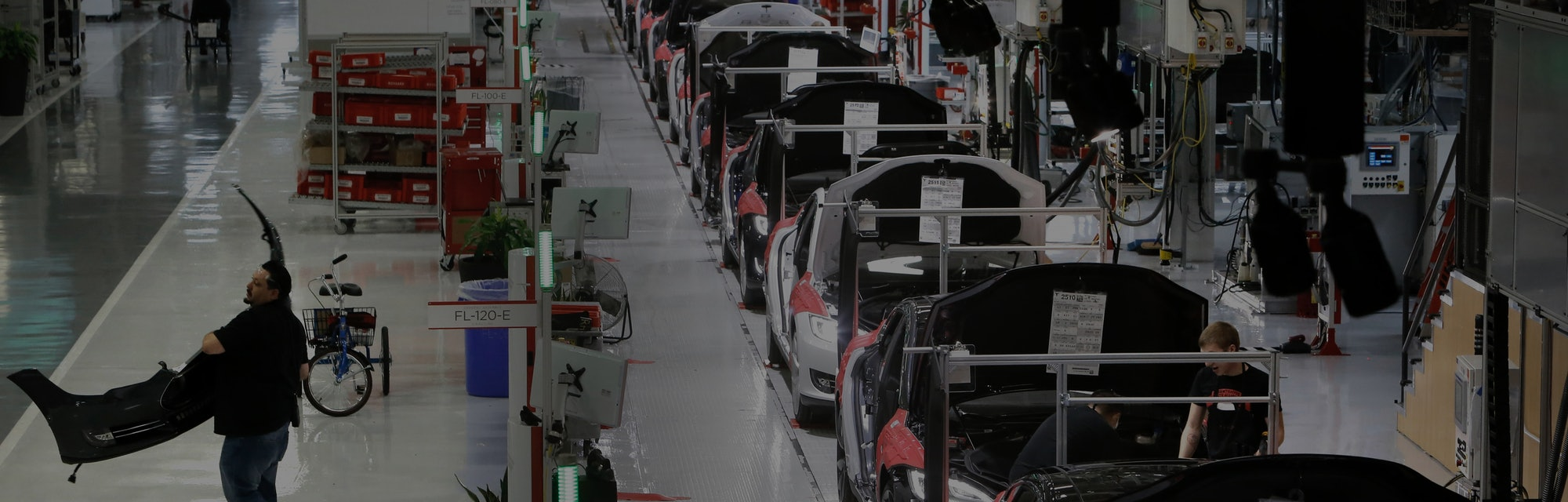 A worker carries a front end part along the assembly at Tesla Motors, California's only full-scale a...