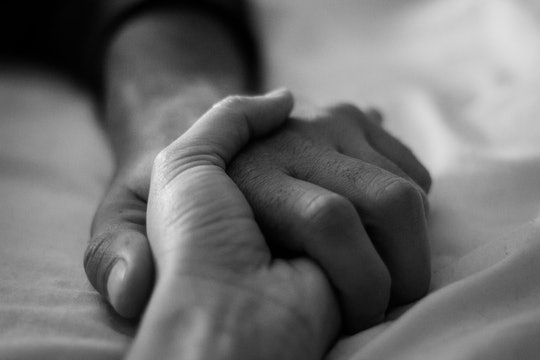 couple holding hands on bed