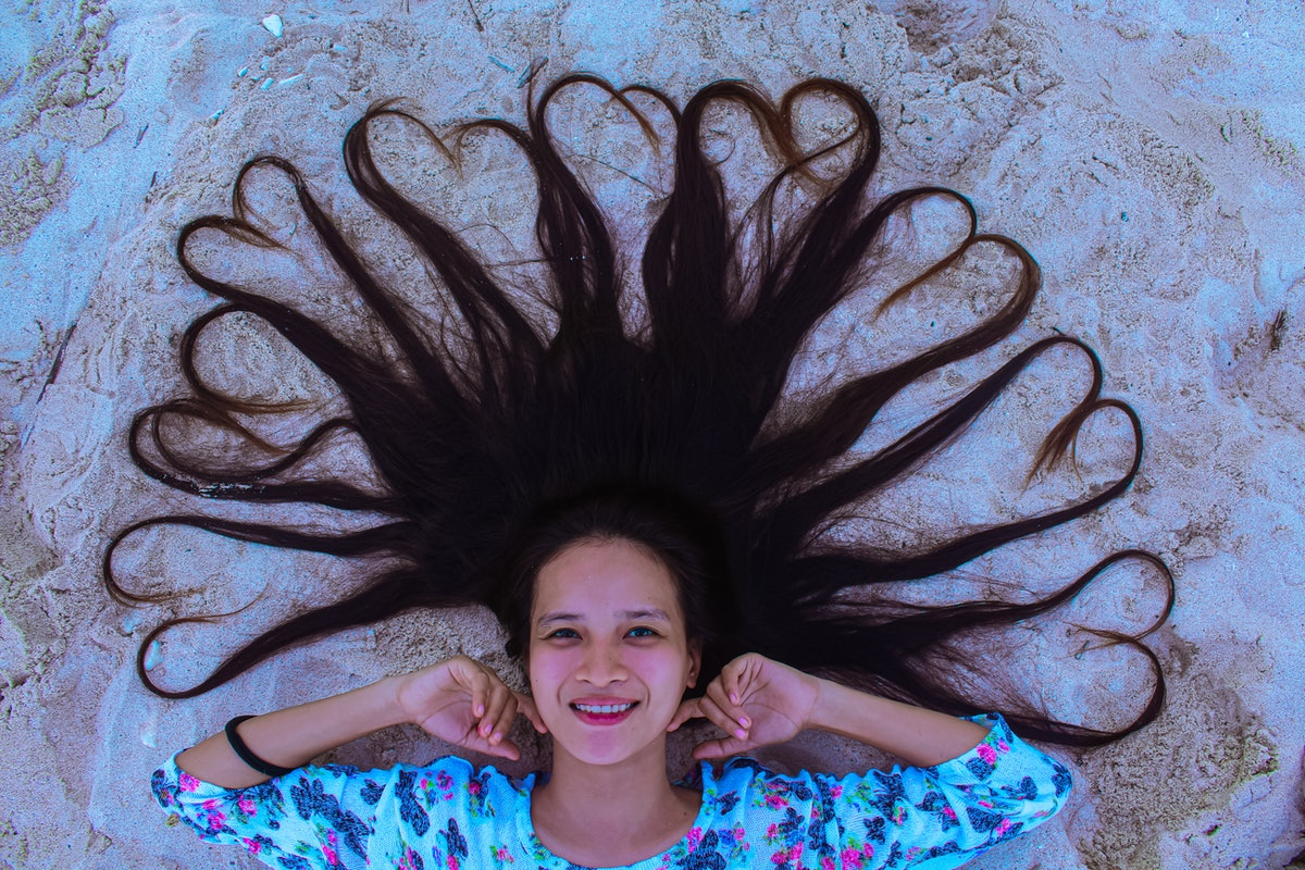 Young woman with her hair shaped in hearts in the sand, having the best week of July 19, 2021, per h...