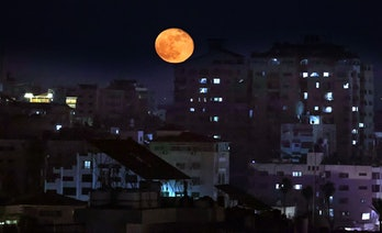 """The """"Super Blood Moon"""" rises above Gaza City in the Palestinian enclave, on May 27, 2021. (Photo by ..."""