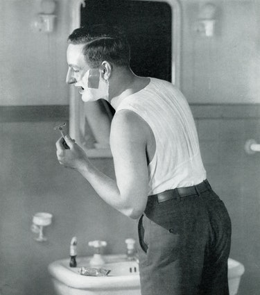 Businessman standing in front of a mirror shaving, from a 1920s guide to salesmanship and selling; s...