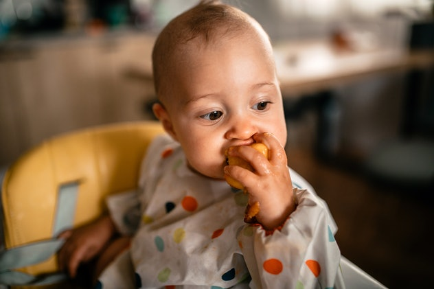 Cute baby girl sitting in the high chair, eating juicy peach