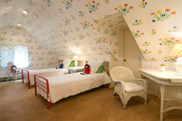 Kids' room interior with two white twin beds and floral wallpaper.