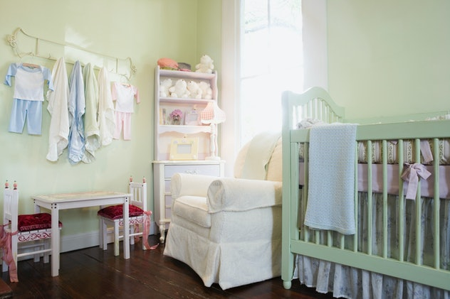Image of a baby nursery with pale yellow walls and pale green crib, with hanging baby clothes on the...