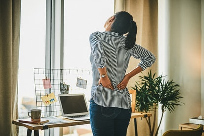 A woman deals with period cramps while working from home. Why are my period cramps so bad all of a s...