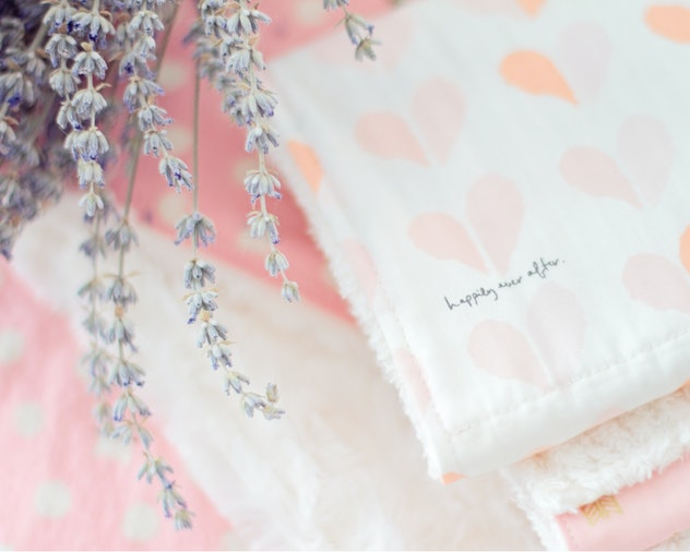 Image of a folded stack of handmade chenille baby burp cloths with lavender flower on top.