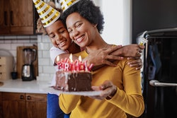 Photo of African American mother and daughter are at home, they are celebrating a birthday