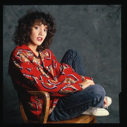 Jennifer Beals with voluminous curly hair and bangs, a signature '80s hair look.