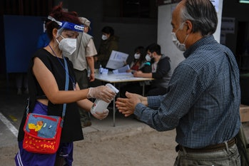 A man sanitizes his hands before casting his ballot in a constitutional referendum voting at a polli...