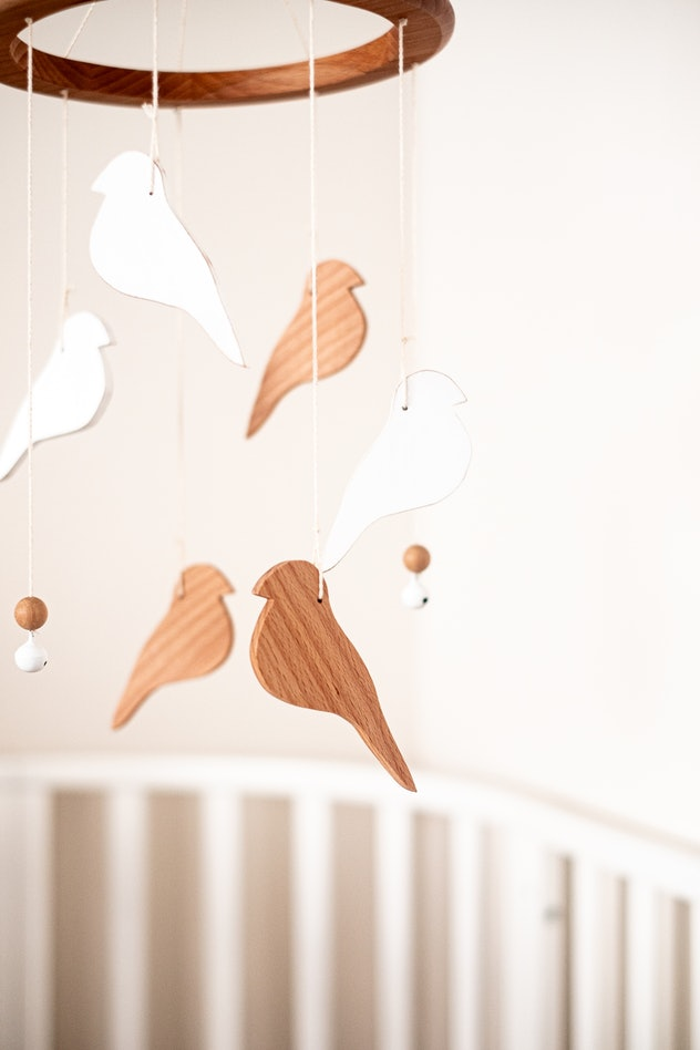 Close-up image of a baby mobile, hanging over a crib, made of wooden bird silhouettes.