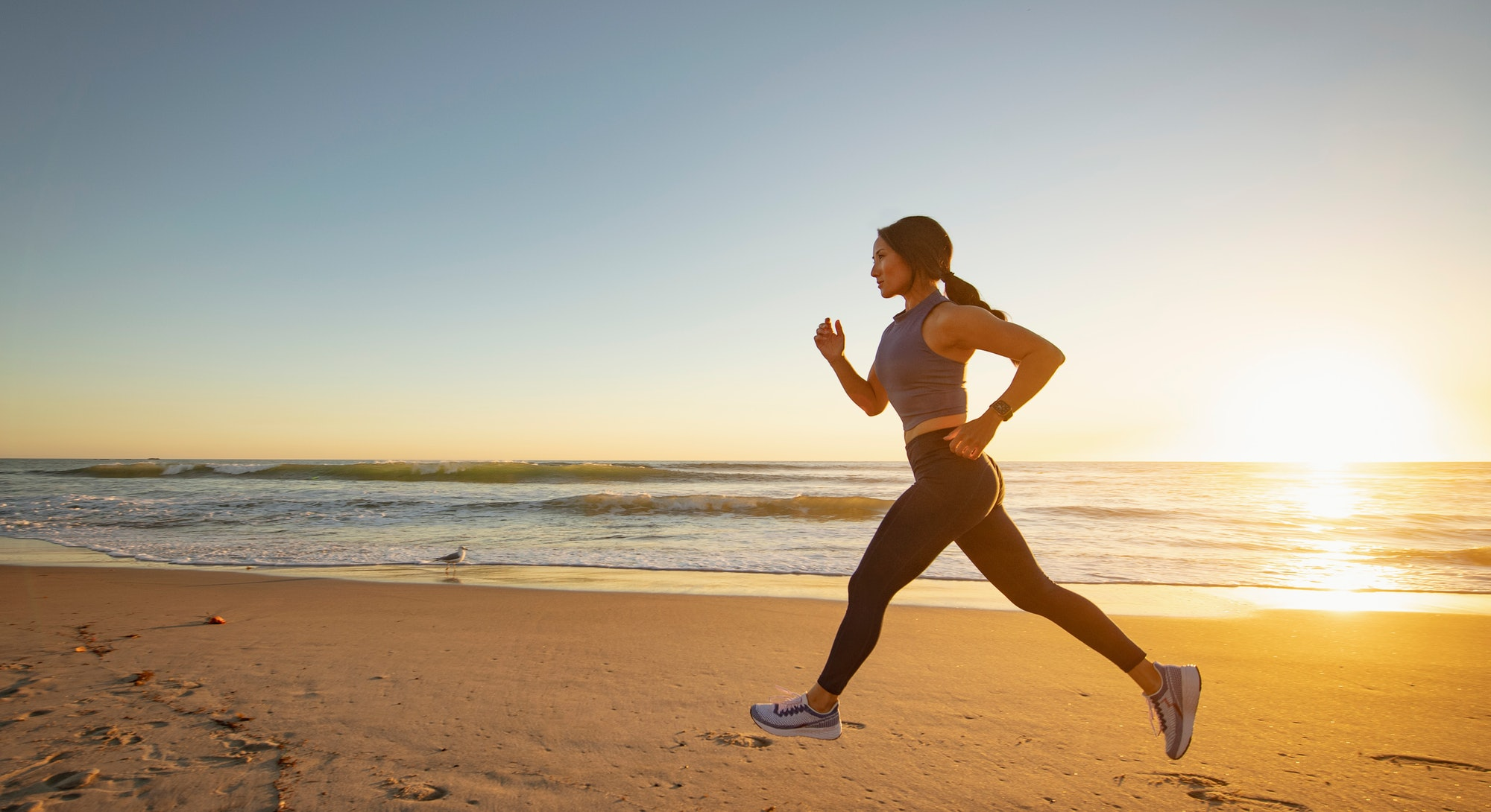 A woman goes running on the beach. You don't need to go swimming to get in a beach workout.