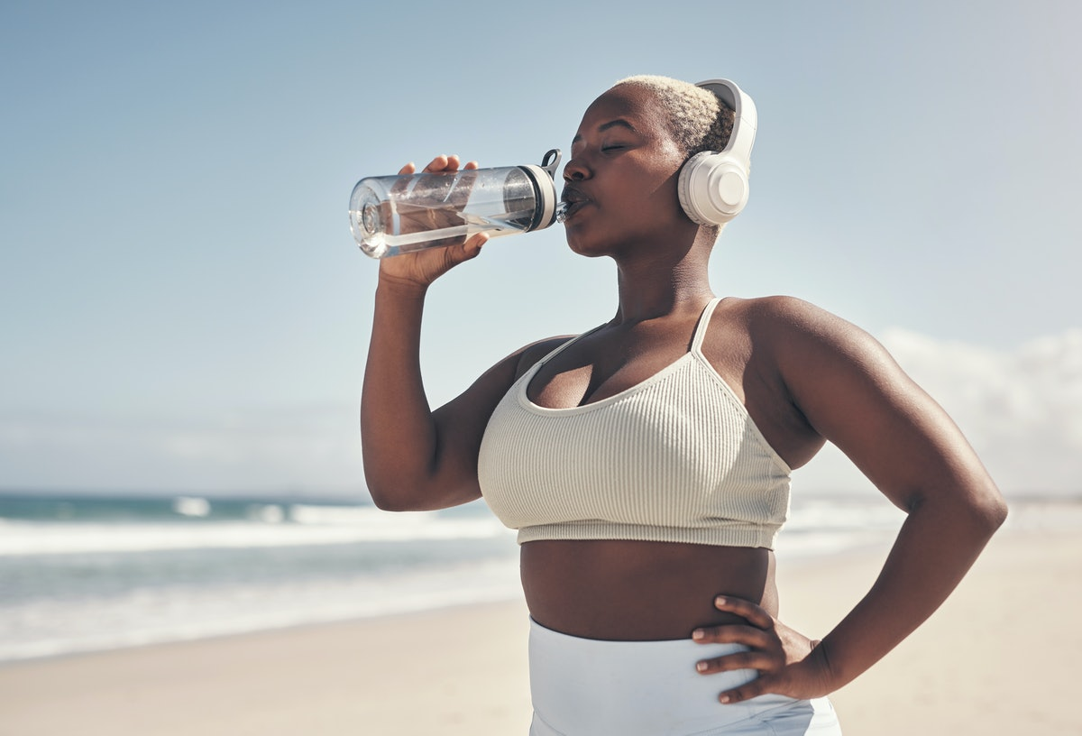 A person drinks from their water bottle during their beach workout. You don't have to swim to work out on the beach.