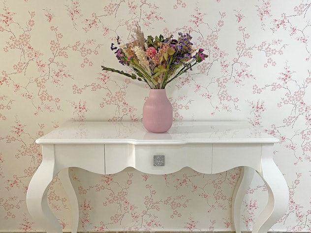 Close-up of a bouquet of dry flowers in a pink jar, perched on a white console table. The wall is co...