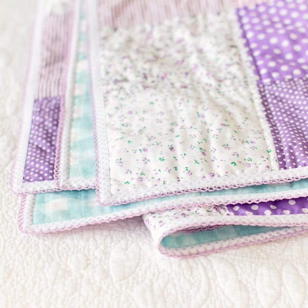 Image of a folded lavender and white baby quilt.
