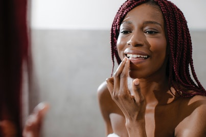 Smiling African woman applying lip balm in front of a mirror.