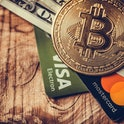 One coin of bitcoin on a black brown with dollars and the cards Visa , Mastercard