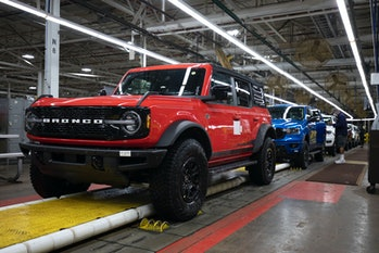WAYNE, MI - JUNE 14: A 2021 Ford Bronco (foreground) and a 2021 Ford Ranger (background) go through ...