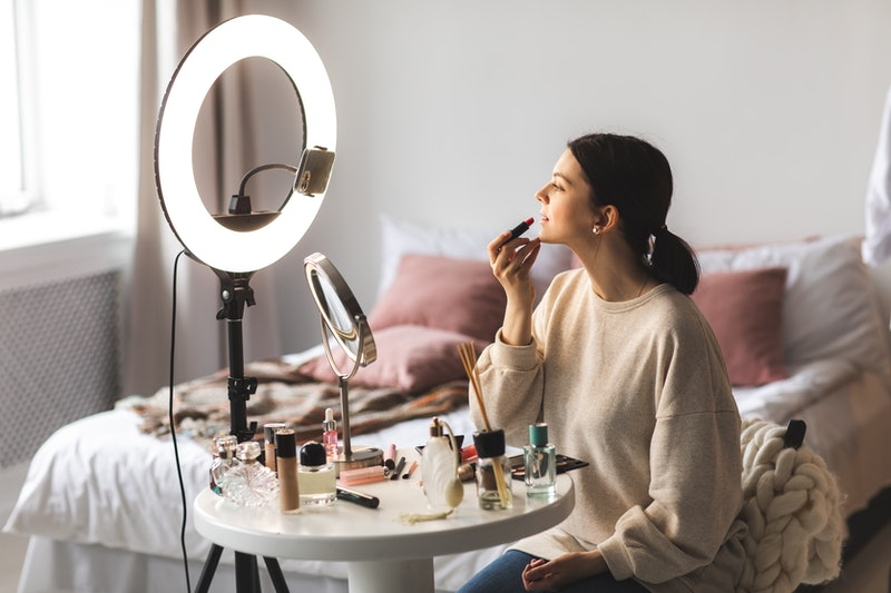 Influencer does make up  to make money on Instagram with exclusive stories.