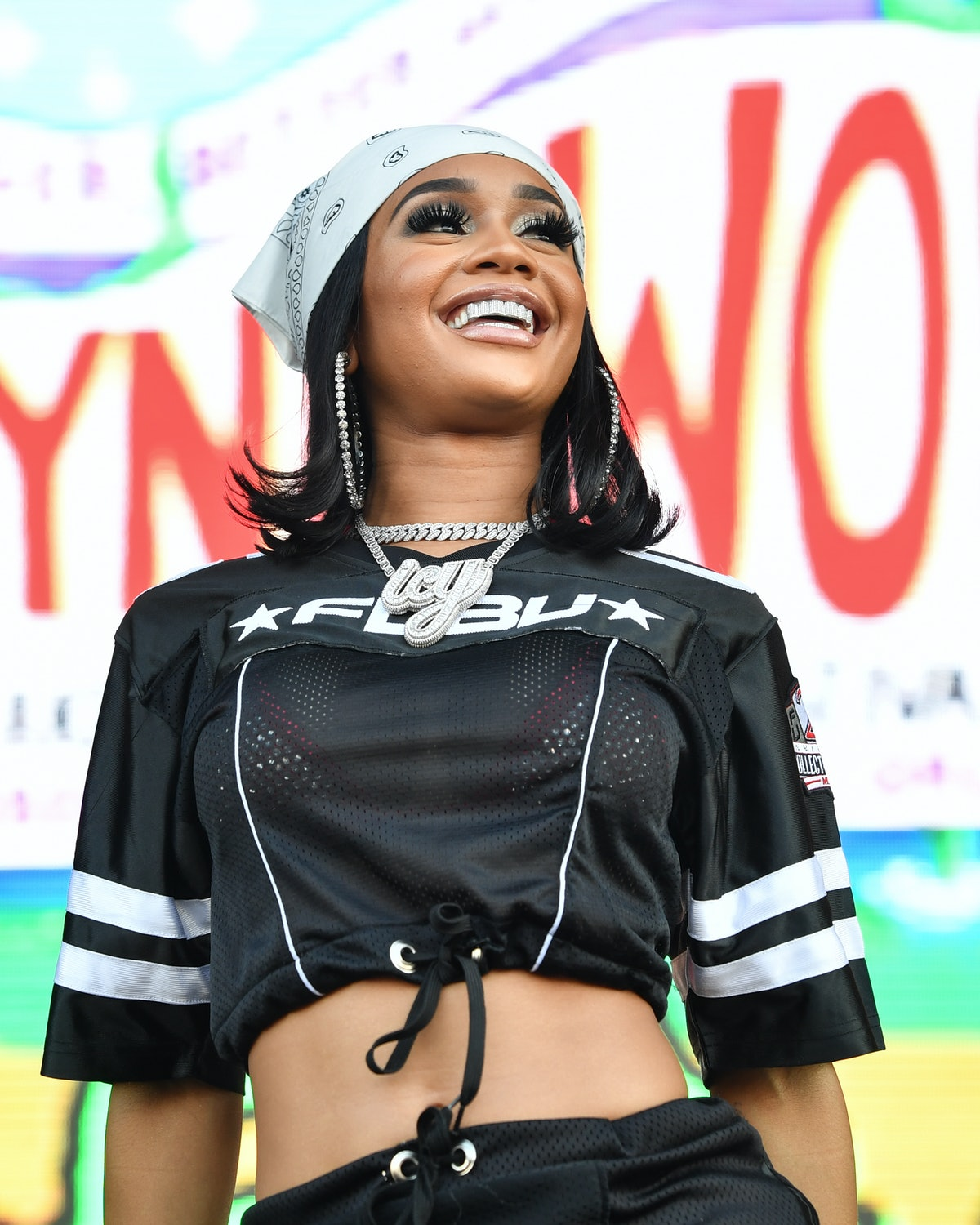 Saweetie performs with her hair cut into a short '70s flip haircut