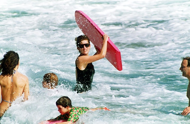 Princess Diana playing with kids in the waves.