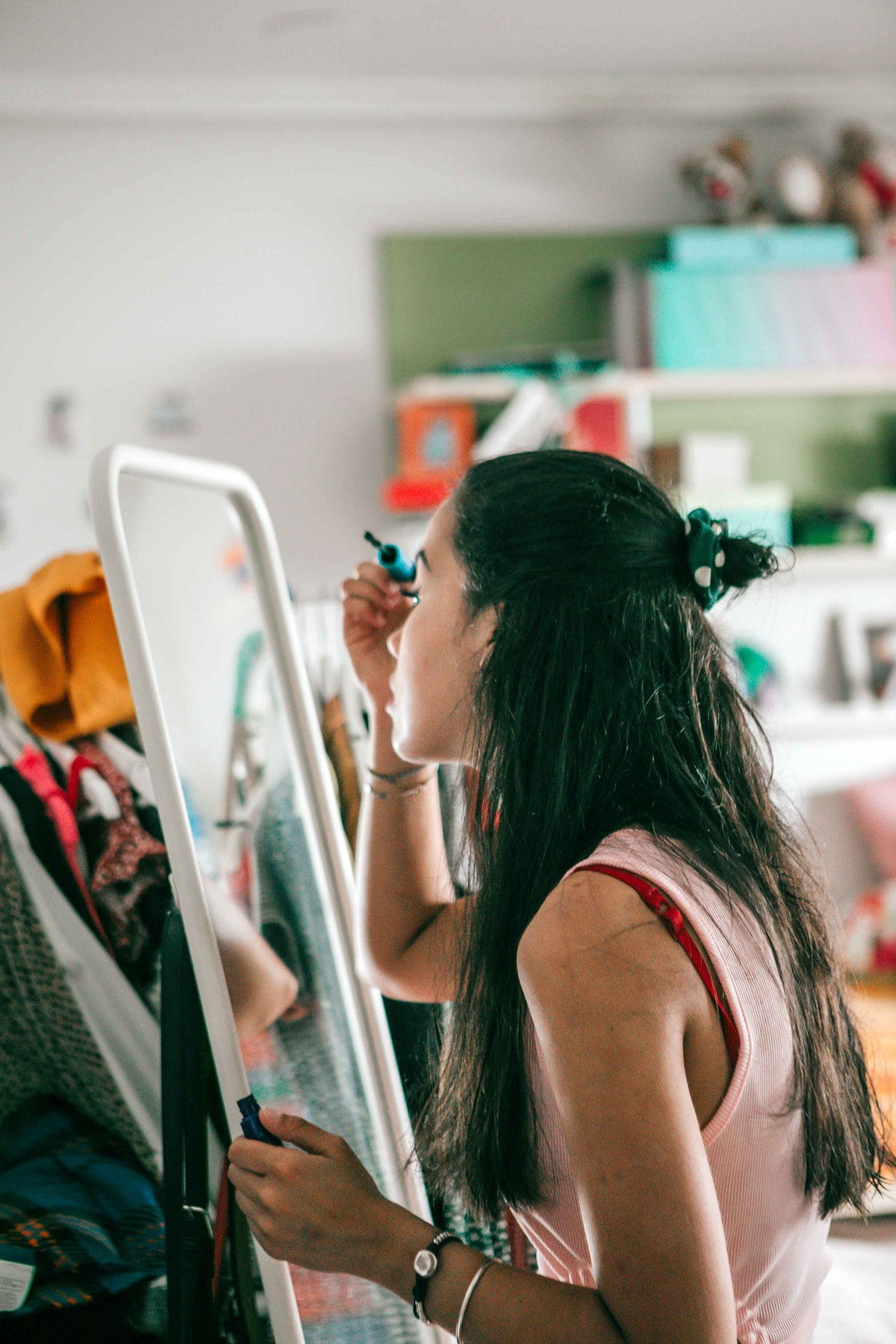 a young woman sitting in front of her bedroom mirror, learning how to apply makeup