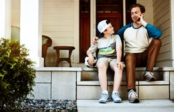 Shot of a father and his son bonding on their porch at home