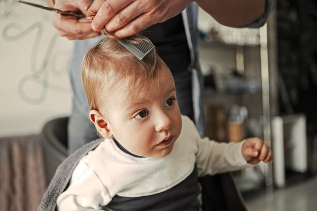 Baby getting his first haircut at hairdresser
