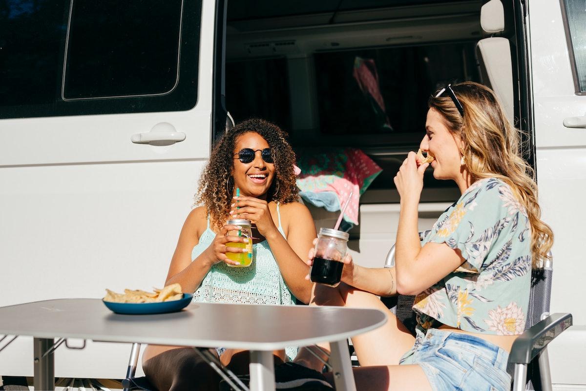 Women enjoying drinks and nachos outside of a van, having TikTok's viral boat dip.