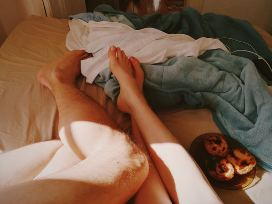 couple's feet in bed together