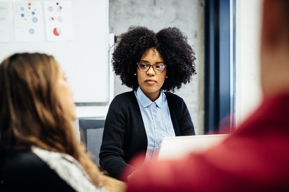 A young black businesswoman wearing glasses listens to team talk during a business meeting in an off...